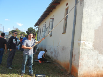 Trevor and students painting church wall