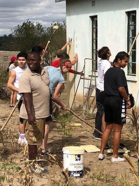 Mitty school students and Victor paint wall of church